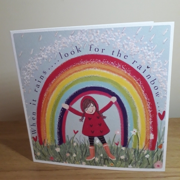 Photo of card with a rainbow and girl.